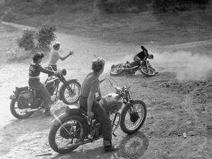 Riders Enjoying Motorcycle Riding, with One Taking a Spill by Loomis Dean