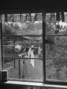 Suburban Housewife Hanging Out a Bit of Laundry, Seen Through Window in typical California Home by Loomis Dean