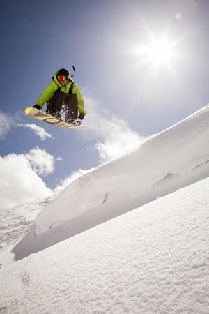 A Young Snowboarder Catching Air in the Wasatch Backcountry, Utah