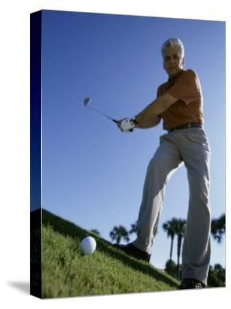 Low Angle View of a Senior Man Swinging a Golf Club