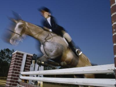 Low Angle View of a Woman Riding a Horse Over a Hurdle--Photographic Print