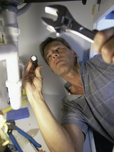 Low Angle View of a Young Man Checking the Plumbing with a Flashlight