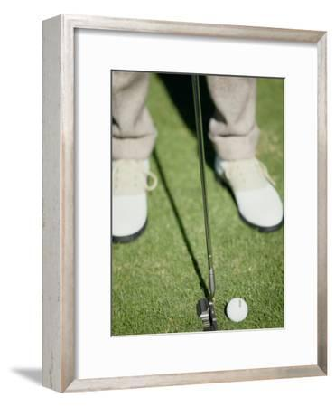 Low Section View of a Man Putting a Golf Ball
