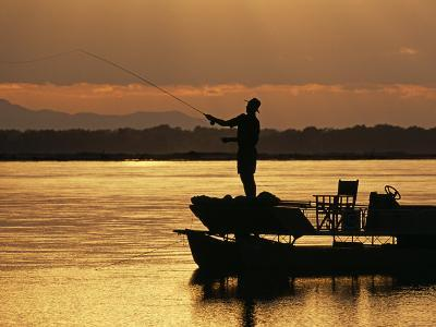 Lower Zambezi National Park, Fly Fishing for Tiger Fish from a Barge on the Zambezi River at Dawn, -John Warburton-lee-Photographic Print