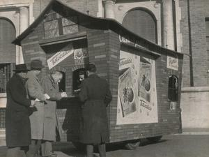 Some Men Play the Ticket at a Totocalcio Receiving Office Shaped House on Wheels by Luigi Leoni