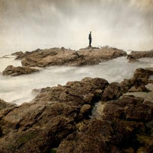 A Lone Man Standing on Large Rocks with the Seas Swirling around Them by Luis Beltran