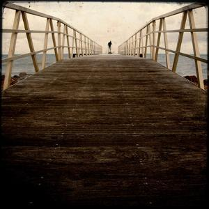 A Long Wooden Walkway at the Sea with a Figure Standing in the Distance by Luis Beltran