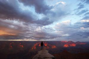 A Man Looking Out over the Grand Canyon at Sunrise from a Rock Promontory by Luis Lamar