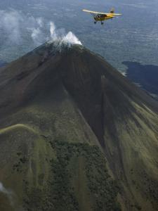 Plane Flies over a Smoking Volcano Called Momotombo by Luis Marden