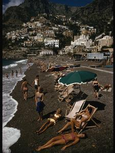 Sunbathers Lounge on a Pebbled Beach by Whitewashed Houses on a Cliff by Luis Marden