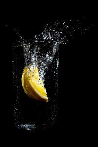 Orange Dropped into a Glass of Water by Luke Peterson Photography