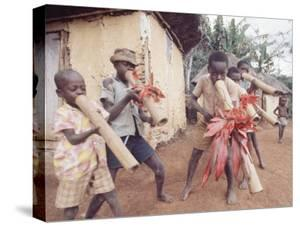 Haitian Children Playing Long Cylindrical Musical Instruments Made of Bamboo by Lynn Pelham
