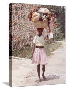Haitian Woman Carrying Large Basket with Her Market Shopping on Her Head by Lynn Pelham