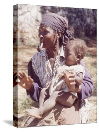 Haitian Woman Smoking a Pipe while Holding a Baby
