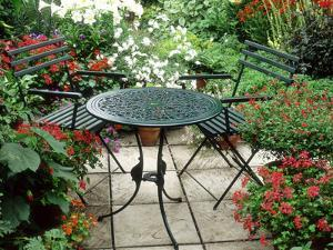 Metal Table and Chairs on Patio Backed by Pots with Lilium Longifolium by Lynne Brotchie