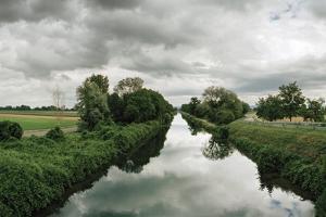 A Canal Cuts Through a Landscape Near the Rhine River by Macduff Everton