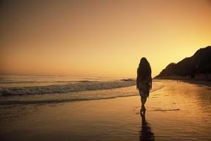 A Woman Walking on Beach at Sunset by Macduff Everton