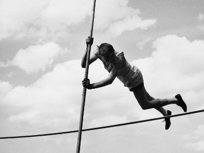 Male Pole-Vaulter Clearing Bar--Photographic Print