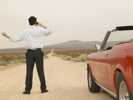 Male Young Adult on Cell Phone with Broken Down Car--Photographic Print