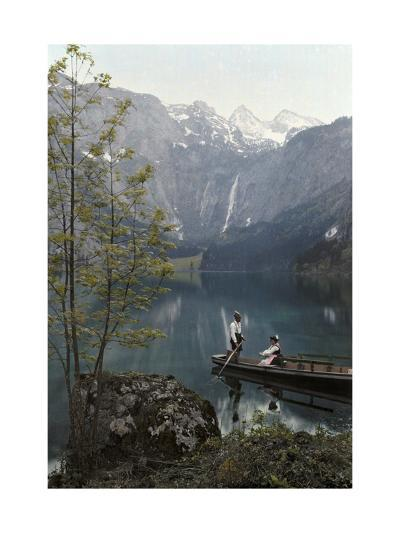 Man and Woman Row in a Boat on the Obersee Lake Near the Mountains-Hans Hildenbrand-Photographic Print
