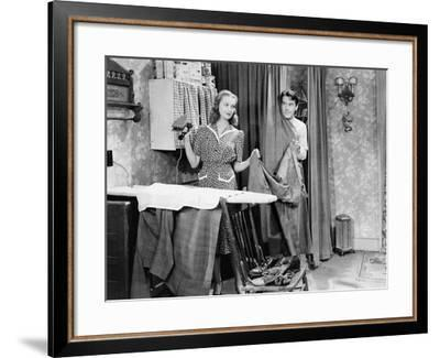 Man and Woman Standing in a Kitchen While She is Ironing His Pants and He is Behind a Curtain--Framed Photo
