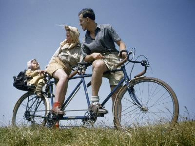 Man and Woman Straddling Tandem Bicycle Look at Child in Back Seat-B^ Anthony Stewart-Photographic Print
