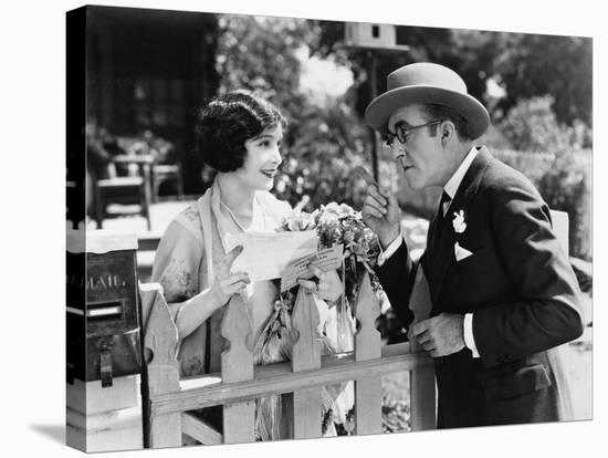 Man and Woman Talking over a Picket Fence--Stretched Canvas Print