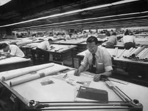 Man at Table with Various Drafting Equipment, Working in Enormous Drafting Room