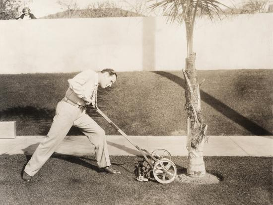 Man Attacking Palm Tree with Lawn Mower--Photo