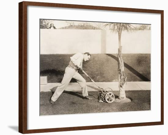 Man Attacking Palm Tree with Lawn Mower--Framed Photo