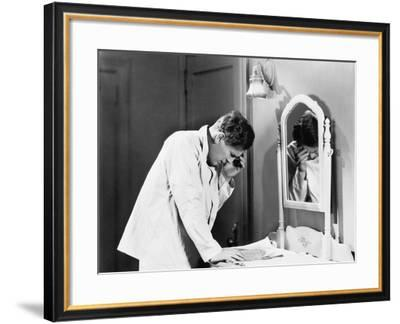 Man Bending over a Piece of Paper on His Dresser and Holding His Head--Framed Photo