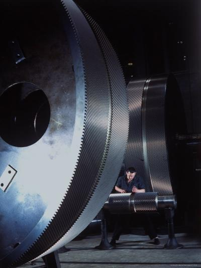Man Dwarfed by Gigantic Gears He is Working on for the Navy, at General Electric Plant in US-Dmitri Kessel-Photographic Print