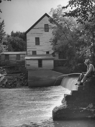 Man Fishing Beside a Waterfall and a 100 Year Old Mill-Bob Landry-Photographic Print