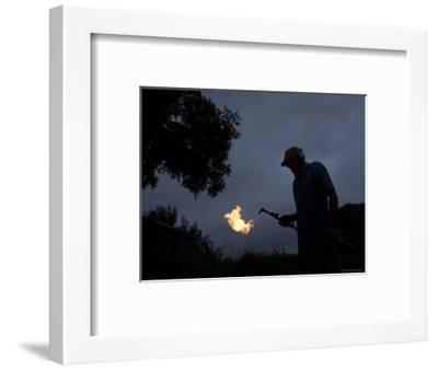 Man Holds a Welding Torch at his Farm near Cortland, Nebraska-Joel Sartore-Framed Photographic Print