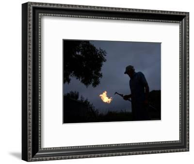 Man Holds a Welding Torch at his Farm near Cortland, Nebraska-Joel Sartore-Framed Photographic Print