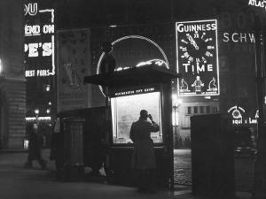 Man in a Raincoat Studies the Westminster City Guide Map at Night in Piccadilly Circus