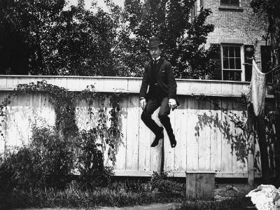 Man in a Suit and Bowler Hat Jumping in the Air in a Backyard in Brooklyn, Ny-Wallace G^ Levison-Photographic Print