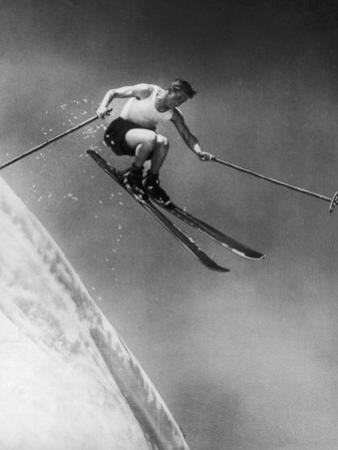 Man in a Vest in Mid-Air as He Skis Down a Steep Mountain