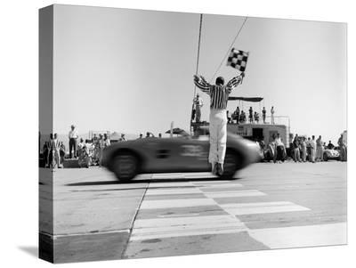 Man jumping waving checkered flag-H^ Armstrong Roberts-Stretched Canvas Print