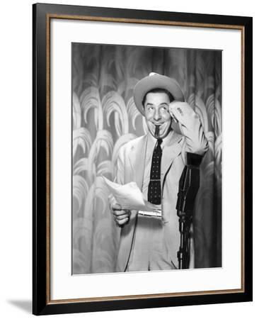 Man Leaning on a Microphone Looking into the Air--Framed Photo