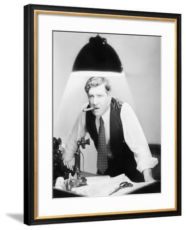 Man Leaning over a Desk with a Ceiling Light Shining on Him--Framed Photo
