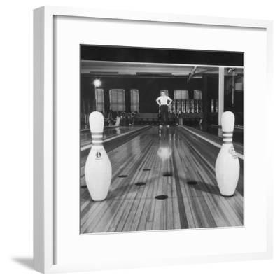 Man Looking at Bowling Pins Left Standing in Lane--Framed Photographic Print