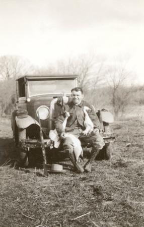 Man on Bumper of Vintage Car with Dead Ducks