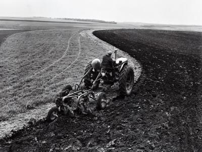 https://imgc.artprintimages.com/img/print/man-on-tractor-dragging-plough-through-vast-field-rear-view_u-l-q10bphh0.jpg?p=0