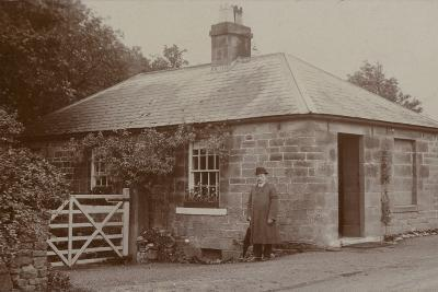 Man Outside a Bungalow--Photographic Print