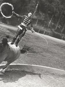 Man Performing Stunt While Standing on Horse