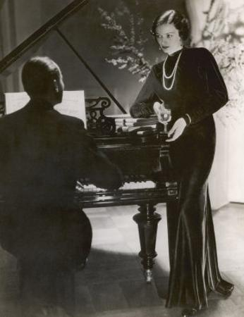 Man Plays a Piano and Looks up at a Glamorous Woman in a Long Dress