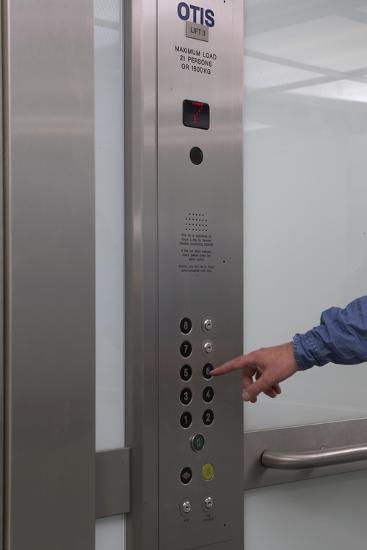 Man Pressing Lift Buttons, UK Office Interior-Richard Bryant-Photo