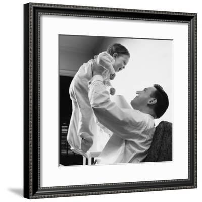 Man Raising Baby Over Head--Framed Photographic Print