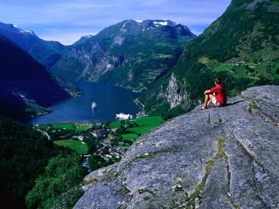 Man Resting on Rock Watching Cruise Ship Sail Out of Geirangerfjord, Geiranger, Norway-Anders Blomqvist-Photographic Print